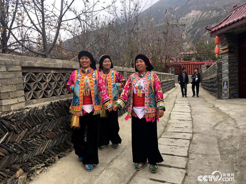 穿着民族服装走在路上的各皂坝村民